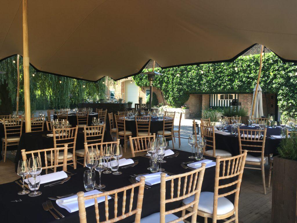 Table rectangulaire et ronde avec le nappage, la vaisselle  et les chaises en bois Natura sous une tente stretch
